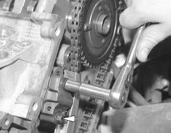 Remove the timing chain tensioner retaining bolts