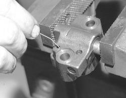 place a paper clip or other suitable tool into the hole in the tensioner body